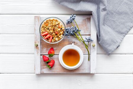 Photo pour Breakfast on the tray with granola, tea and fruit on white wooden background top view - image libre de droit