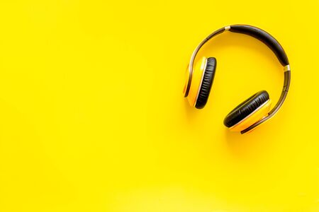 Foto de Audio listening with wireless headphones on yellow background top view space for text - Imagen libre de derechos