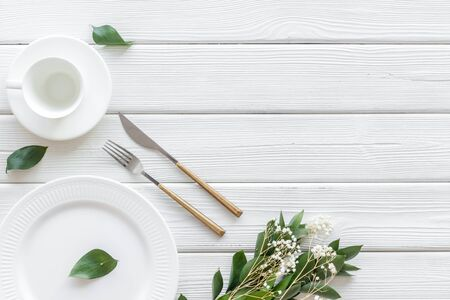 Photo for White plates and flowers for table setting on white wooden background top view mockup - Royalty Free Image