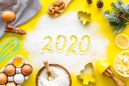 Photo pour Happy New Year concept. 2020 written on yellow baking background top view - image libre de droit