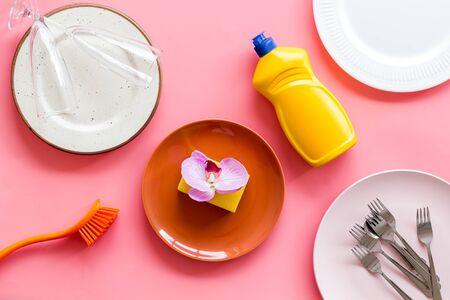 Photo pour Dishwashing liquid bottle near plates on pink background top view - image libre de droit