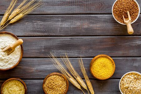 Photo for Healthy food. Cereals - rice, oats, buckwheat - in bowls with ears on dark wooden background top view frame copy space - Royalty Free Image