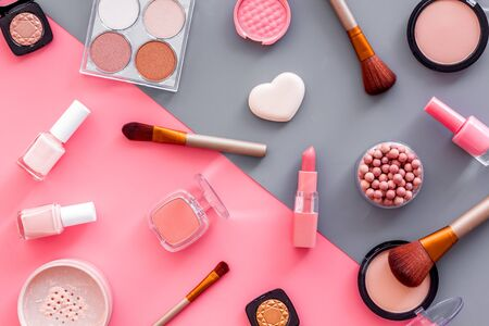 Photo pour Makeup background with rounge, powder and tools on pink and grey table top view. - image libre de droit