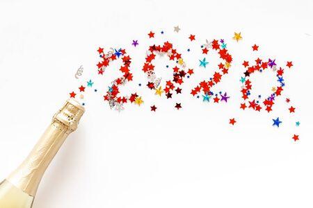 Foto de Celebrate New Year 2020. Date on confetti near champagne bottle on white background top view. - Imagen libre de derechos
