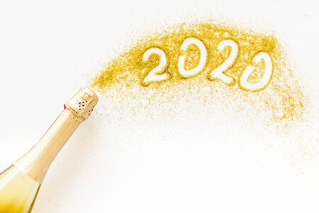Foto de 2020 Happy New Year concept. Date written on golden dust near champagne bottle on white background top view. - Imagen libre de derechos
