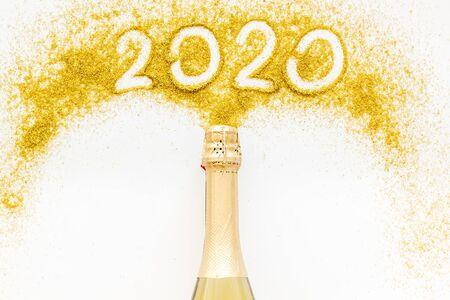 Foto de 2020 Happy New Year concept. Date written on golden dust near champagne bottle on white background top view copy space - Imagen libre de derechos