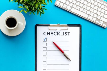 Checklist and pen on blue office background top view