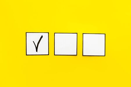 Photo pour Check mark in check-box on yellow background top view copy space - image libre de droit