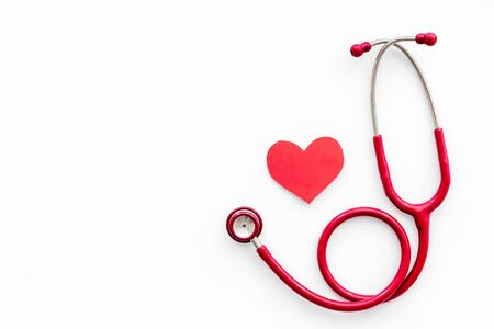 Foto de Health care concept. Heart icon and stethoscope on white background top view. - Imagen libre de derechos