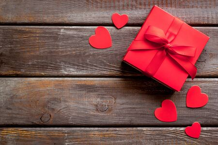 Photo for Gift to a sweetheart on Valentines Day. Red present box near hearts on dark wooden - Royalty Free Image