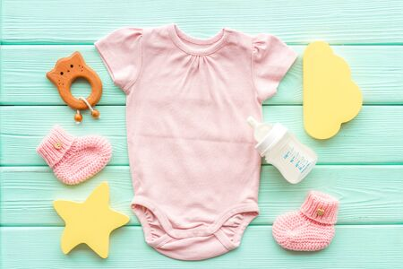 Photo pour Pink bodysuit for baby girl near childrens things on green wooden - image libre de droit
