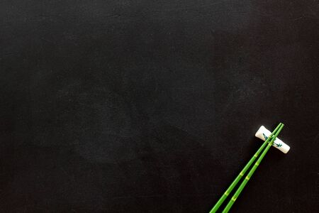 Photo pour Chopsticks - green wooden utensil for sushi and rolls - on black background top-down. - image libre de droit