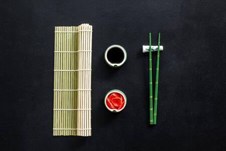 Photo pour Oriental table set up. Chopsticks, ginger, soy sause, bamboo mat on black background top-down. - image libre de droit