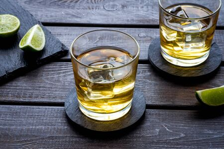 Photo pour Whiskey with ice. To glasses of strong alcohol drink near lime on dark wooden background - image libre de droit