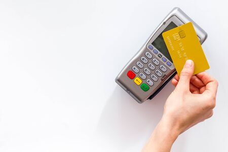 Photo for Contactless payment, paypass. Hand hold bank card near terminal on white background top-down copy space - Royalty Free Image