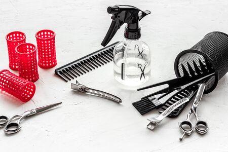 Foto de Hairdresser desk with combs, scicoors, spray and curlers on white background. - Imagen libre de derechos