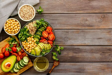 Photo pour Quinoa, avocado and chickpeas in bowl in hands - balanced healthy food - on wooden table. Top view copy space - image libre de droit