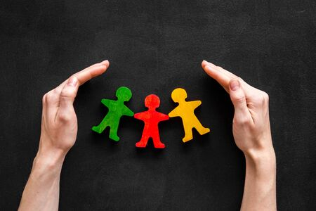 Photo pour Social protection, insurance, security and safety concept. Hands take care of wooden human figures black desk top view - image libre de droit