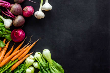 Photo for Flat lay of fresh vegetables and greenery on black table top-down copy space - Royalty Free Image