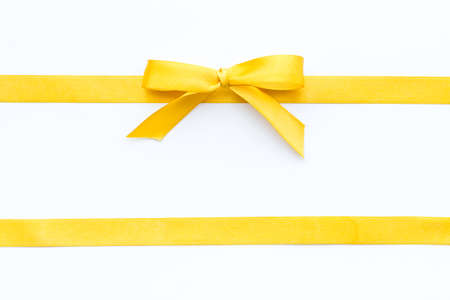 Photo pour Yellow ribbon bow isolated on white background, top view, copy space - image libre de droit
