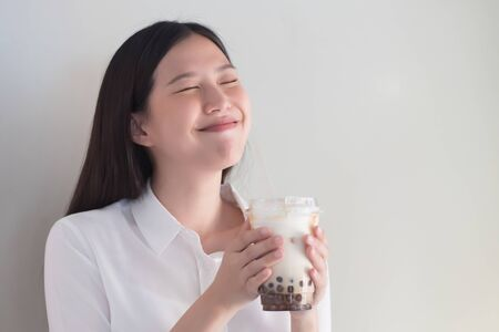 Photo pour Happy smiling asian woman drinking iced bubble milk tea; aka boba tea, pearl milk tea, tapioca tea, asian exotic beverage concept - image libre de droit