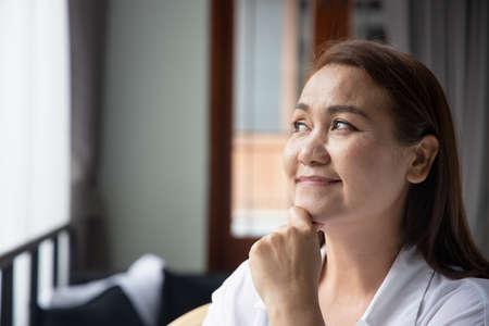 Photo pour happy middle aged woman thinking, looking up - image libre de droit