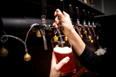 Foto de Bartender pours fresh ale from tap in tap. - Imagen libre de derechos