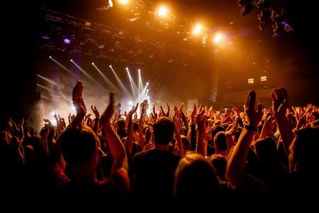 Photo pour Crowd on music show, happy people with raised hands. Orange stage light - image libre de droit