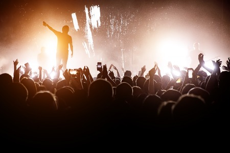 Foto de Rock concert. Leader on the stage. Silhouette of the crowd in front of the stage - Imagen libre de derechos