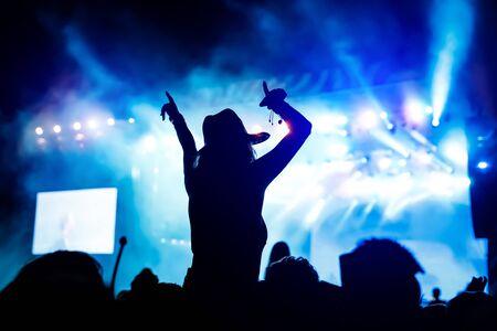 Photo pour Silhouette of girl with raised hands on music concert. - image libre de droit