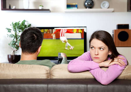 Image of woman getting bored, while her partner watching sports