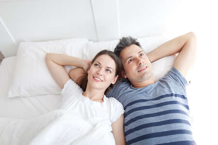 Young couple lying on bed, relaxing