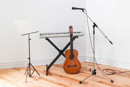Musical instruments in a room. Electric piano, guitar, microphone and stand with sheet music.