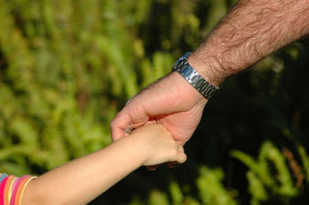 White hands of caucasian father and child holding hands while walking together in the park outdoors