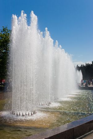 Fountains with parallel spurts in city park in sunny summer day