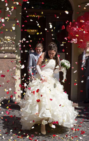 Newly married shower with petals of roses and coins