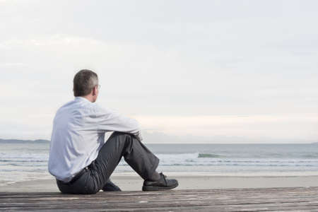 Thoughtful businessman sitting on a beach and looking at the sea
