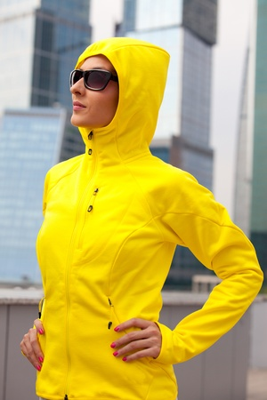 portrait of a young girl in a yellow hood with black sunglasses