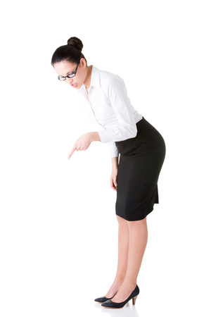Young business woman bending down and looking. Isolated on white.