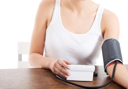 Woman measures her blood pressure.