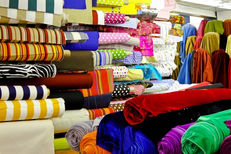 Assortment of colourful textile fabric rolls in warehouse
