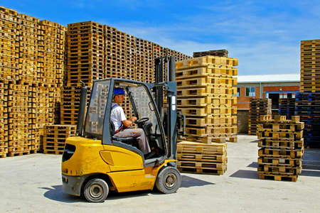 Forklift operator handling wooden pallets in warehouse