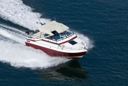 A red runabout shot from above while travelling fast.