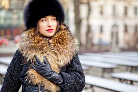 Winter girl wearing expensive real fur and leather gloves in autumn