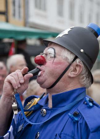 SVENDBORG, DK - MAY 22:  Clown  P C Bluey blowing  his whistle  in the street during 12th International Clown Festival   May 22, 2010 Svendborg, Denmark.