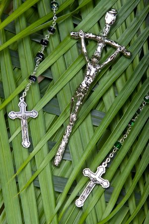 close up of rosaries and crucifx on palm leaves