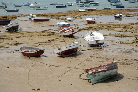 Small fishing boats while low tide on the ocean bed