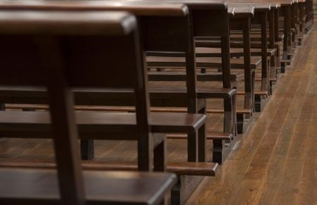 Empty brown wooden benches in a church