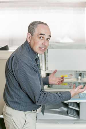 Business man having problem with photocopy machine in office looking frustrated and angry