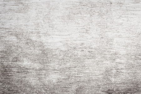 Gray wooden background of weathered distressed rustic wood with faded white paint showing woodgrain texture